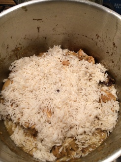 layering the rice with the chicken curry