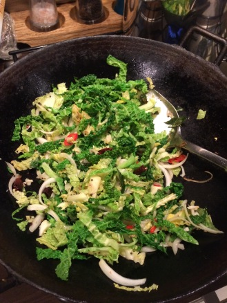 stir frying Savoy cabbage with the spices, onions and curry leaves