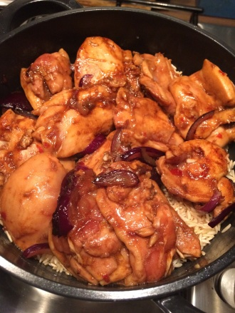 Placing chicken & onions on top of the rice